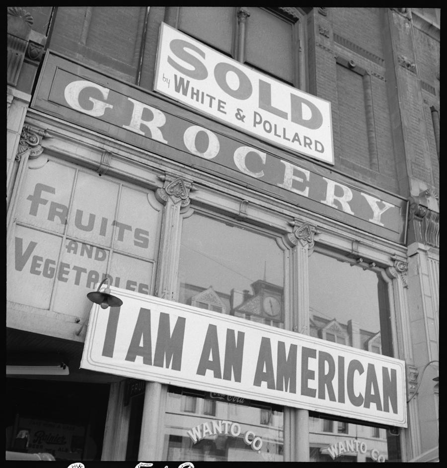 """Oakland, Californie.  Le propriétaire de cette boutique, un diplômé de l'Université de Californie d'ascendance japonaise, a accroché ce panneau """"I AM AMERICAN"""" (je suis américain) le 8 décembre 1941, le lendemain de l'attaque japonaise sur Pearl Harbor. Suite à l'ordre d'évacuation, la boutique fut fermée en avril 1942."""