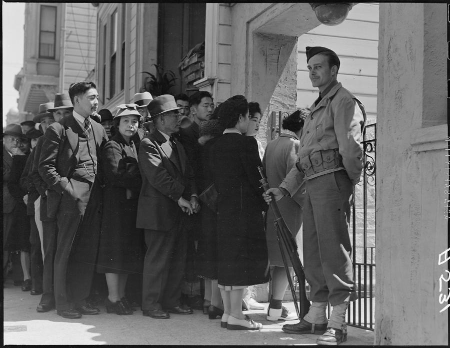 """San Francisco, Californie. Les chefs des familles d'origine japonaise, ainsi que les personnes vivant seules, font la queue devant un office de contrôle civil, situé dans le Japanese American Citizens League Auditorium afin d'être """"pris en charge"""" à la suite du Civilian Exclusion Order n°20."""