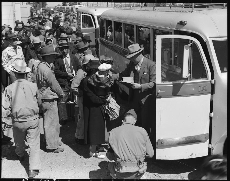 Fermiers montant à bord de bus à destination du Turlock Assembly Center. Un responsable se charge de faire monter les familles en se basant sur leurs numéros de tri.