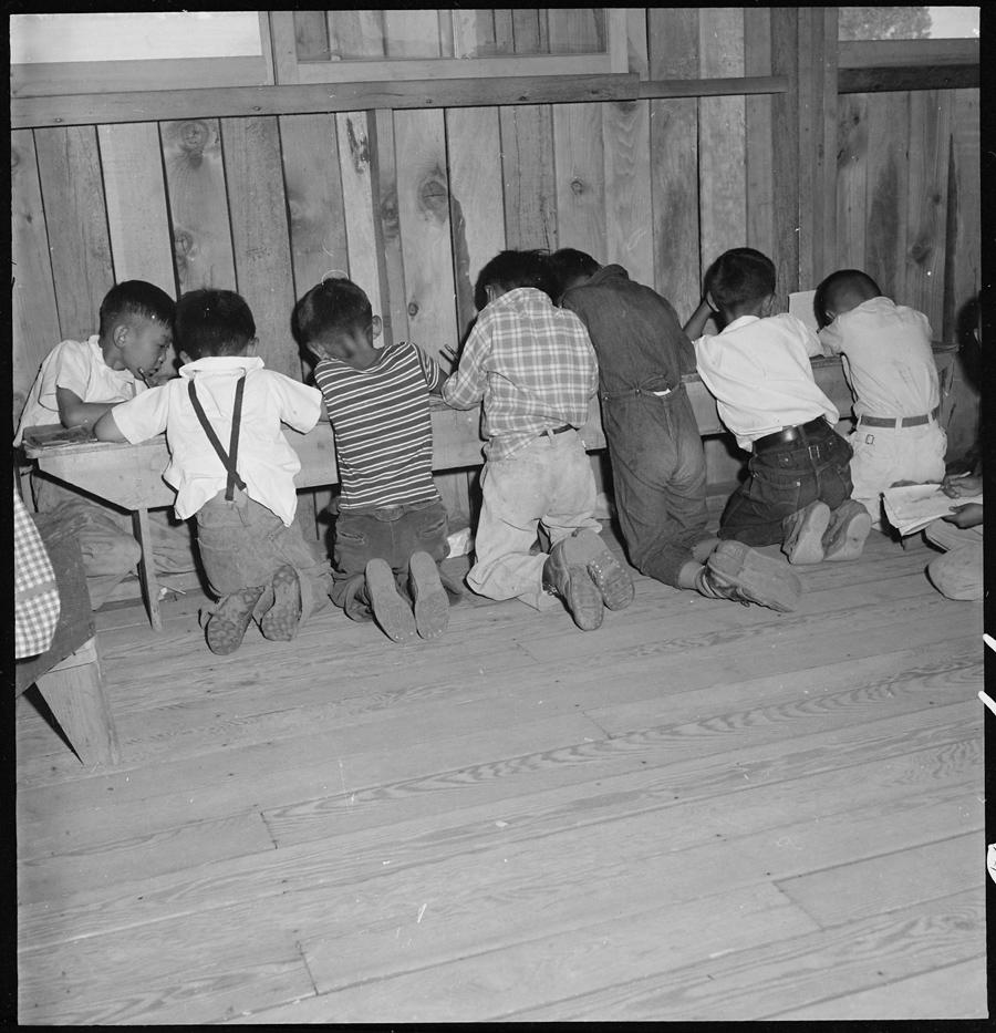Centre de déportation de Manzanar, Californie. Des enfants apprennent leurs leçons de mathématiques. Les équipements scolaires n'étaient pas disponibles au moment où cette photo fut prise.